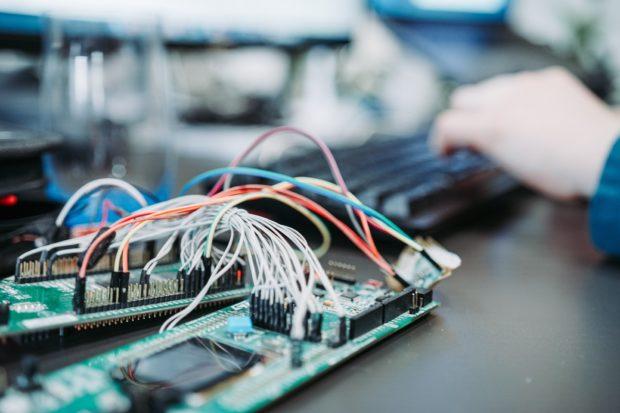 person using computer keyboard near green circuit board