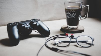 black Sony Dualshock 4 beside clear glass mug filled with coffee